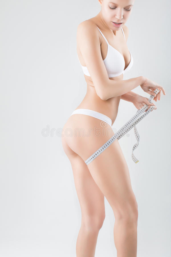Schöner sportlicher Frauenkörper mit gelbem Maß lizenzfreie stockbilder