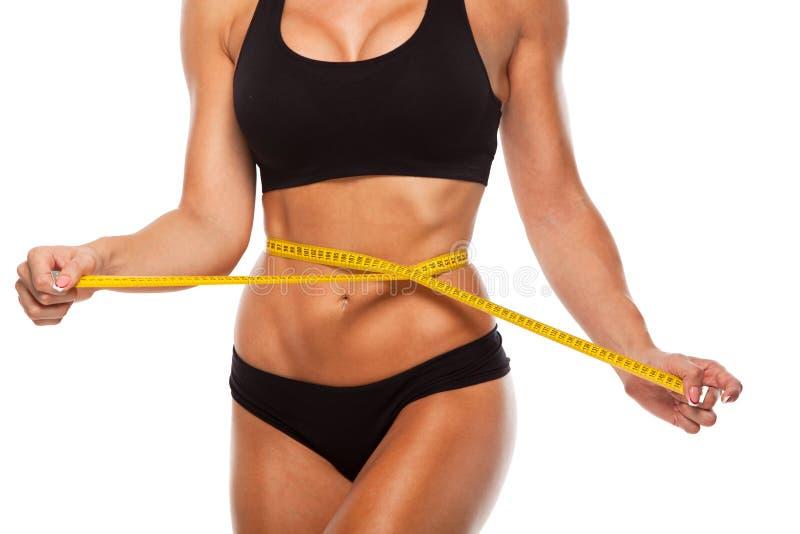 Schöner sportlicher Frauenkörper mit gelbem Maß an stockfotos