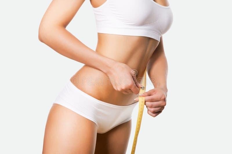 Schöner sportlicher Frauenkörper mit Maß stockbild
