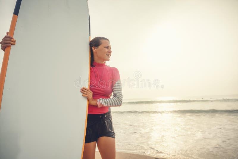 Schöner sportlicher nasser Mädchensurferanfänger steht mit einem sur lizenzfreie stockfotografie