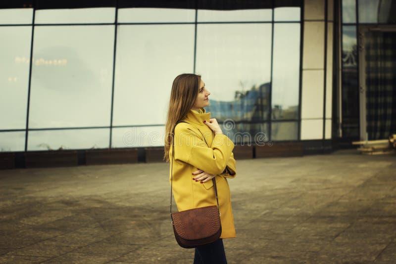 Schöner Stand der jungen Frau auf der backround der hohen Gebäude im Frühjahr Zeit stockbild