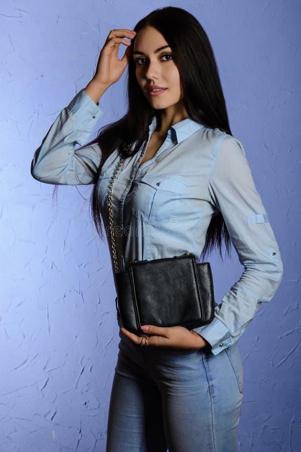 Schöner stilvoller Brunette in den Jeans, die eine schwarze Kupplung halten lizenzfreie stockfotografie