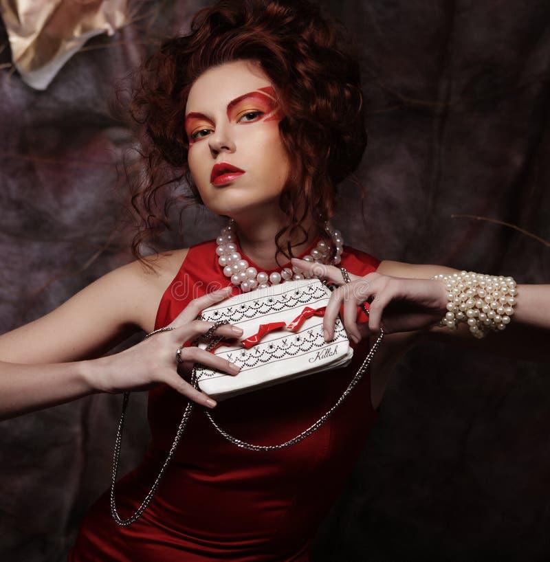Schöner stilvoller Brunette in einem roten Kleid hält eine Handtasche stockfoto