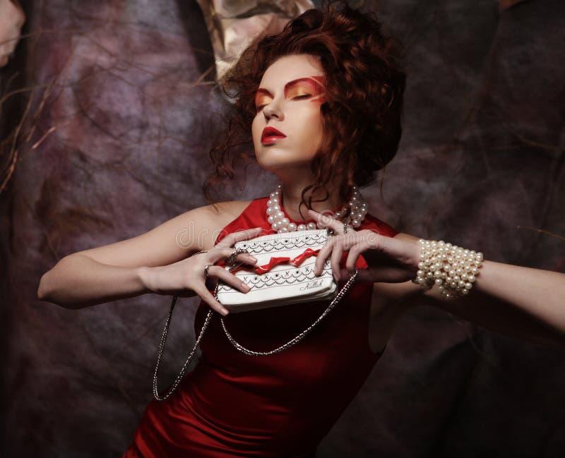 Schöner stilvoller Brunette in einem roten Kleid hält eine Handtasche stockfotografie