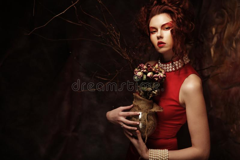 Schöner stilvoller Brunette im roten Kleid, das einen Blumenstrauß von dri hält stockfotos