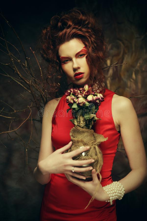 Schöner stilvoller Brunette im roten Kleid, das einen Blumenstrauß von Trockenblumen hält lizenzfreie stockbilder