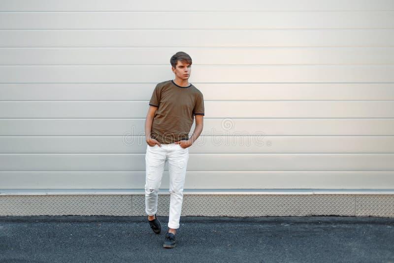 Schöner stilvoller junger Mann in einem Mode T-Shirt und in weißen Hosen stockfotografie