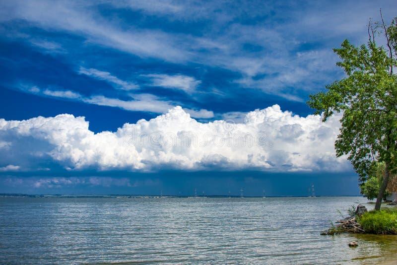 Schöner Strand auf dem Hintergrund eines ungewöhnlichen bewölkten Himmels stockbilder