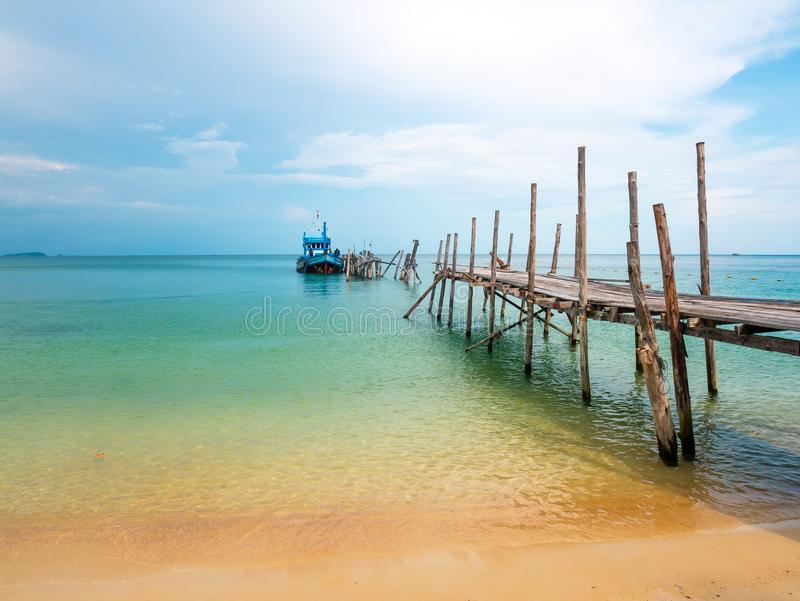 Schöner Strand mit blauem Himmel und einem Boot auf dem Dock stockfoto