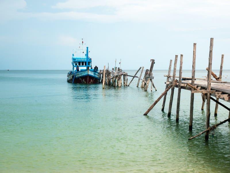Schöner Strand mit blauem Himmel und einem Boot auf dem Dock stockbild