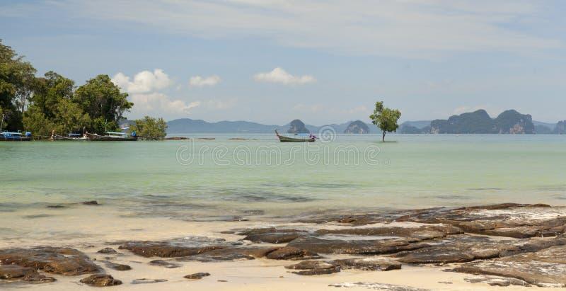 Schöner Strand mit Seeansichten und einem traditionellen thailändischen Fischerboot Schöner Strand mit tropischen Bäumen mit eine stockbilder