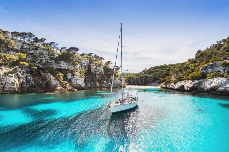 Schöner Strand mit Segelbootyacht, Cala Macarelleta, Menorca-Insel, Spanien Segelsport, Reise und aktives Lebensstilkonzept stockbild