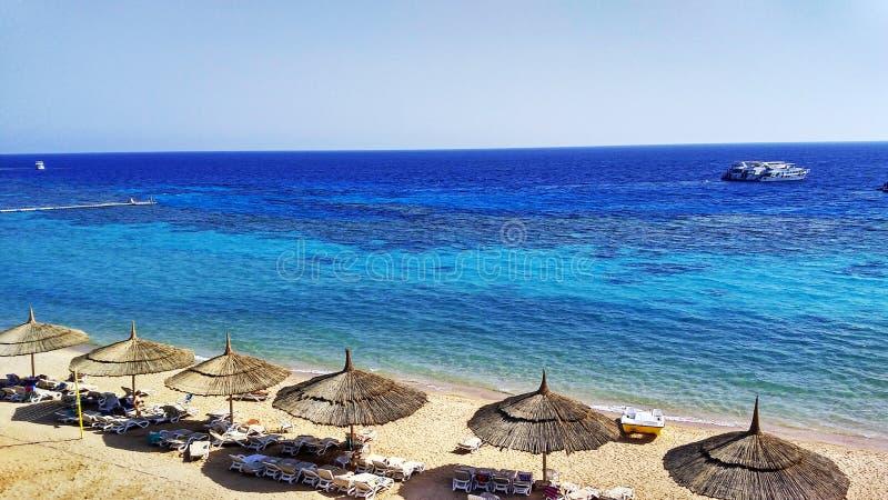 Schöner Strand mit strawy Sonnenschirmen und überraschendem blauem Meer stockbilder