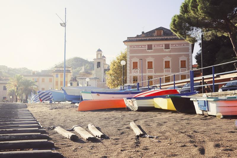Schöner Strand mit und bunten Booten den mit gelbem Sand in der alten italienischen Stadt Sestri Levante Ligurien auf Sonnenunter stockfotografie