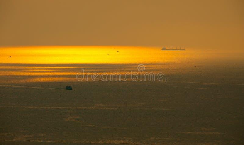 Schöner szenischer goldener Sonnenstrahl in dem Meer vor Sonnenuntergang am populären Strand im Sommer teils im Dunst stockfotografie