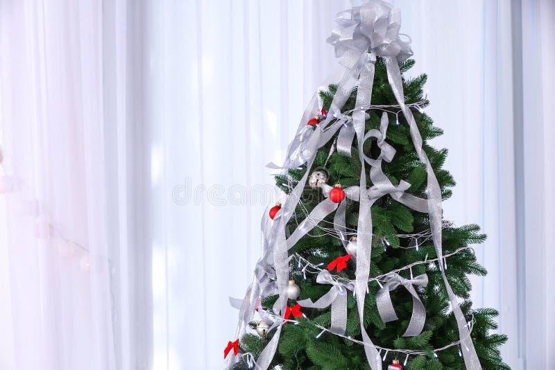 Schöner Tannenbaum mit silbernen Bändern und Weihnachtslichtern stockfotos