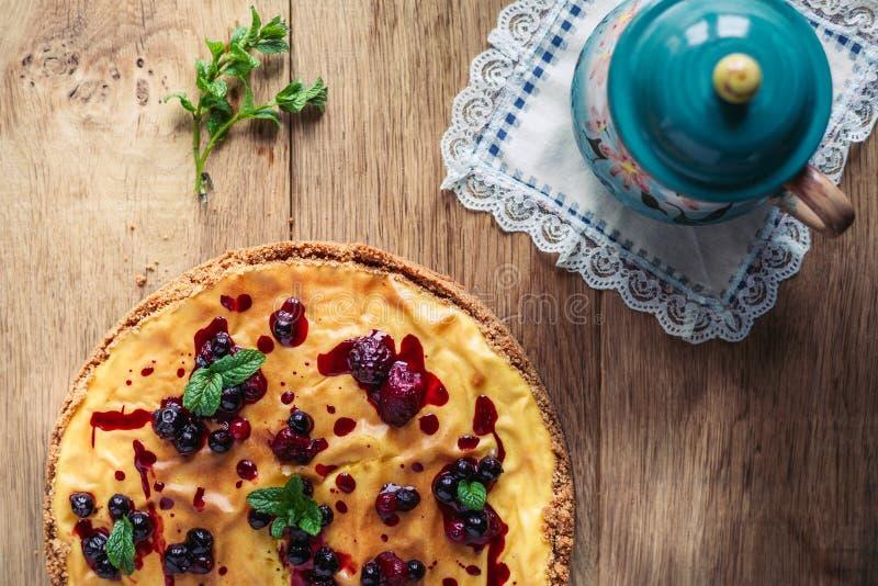 Schöner traditioneller italienischer Käsekuchen mit roten Früchten, Minze und Puderzucker auf hölzernem Hintergrund, selektiver F stockfotografie