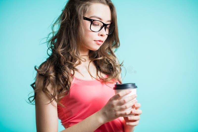 Schöner trinkender Kaffee der jungen Frau Junge Brunettefrau, die eine Papierschale auf ihrer Hand auf einem blauen Hintergrund h lizenzfreie stockfotografie