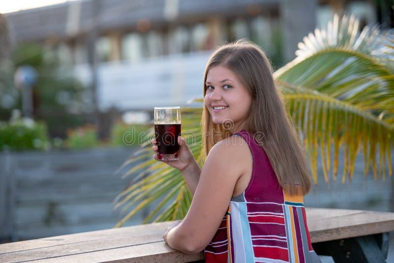 Schöner trinkender Saft der jungen Frau auf Strand stockfoto