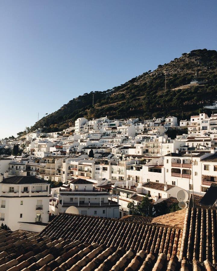 Schöner vertikaler Schuss von weißen Häusern und Dachspitzen einer kleinen Küstenstadt in Spanien lizenzfreie stockfotografie