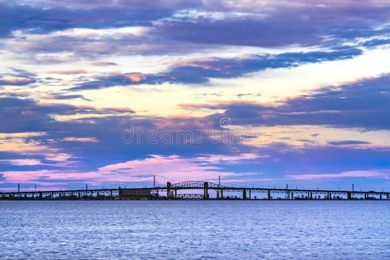 Schöner violetter, blauer und gelber Sonnenuntergang über langem silhouettiertem s lizenzfreie stockbilder