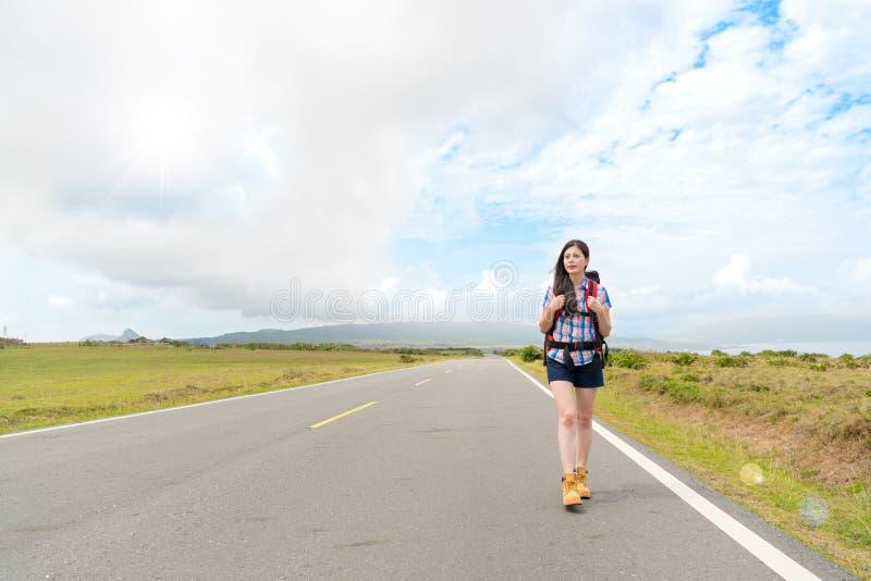 Schöner Wanderer junger Dame, der auf weiten Weg geht stockfoto