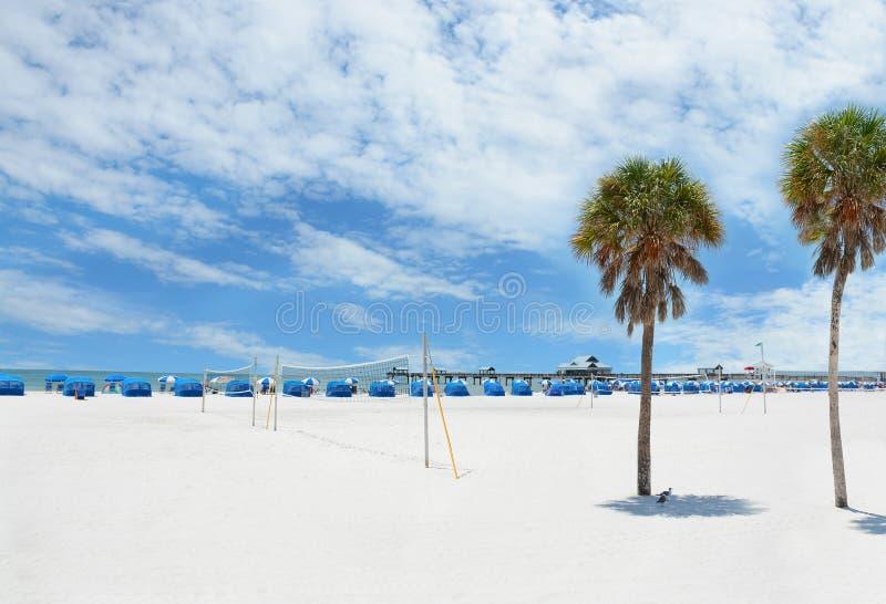 Schöner weißer Strand mit Palmen und Pier lizenzfreie stockfotografie