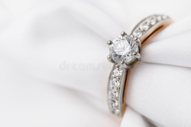 Schöner weißes und gelbes Goldring mit Zirkon und ein Diamant auf Seidengewebe mit Kopienraum stockfotografie