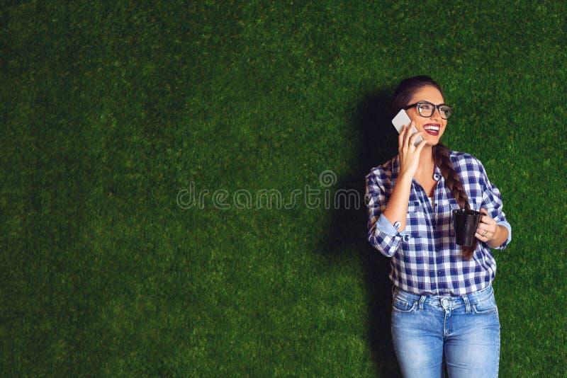 Schöner weiblicher Architekt auf einer Kaffeepause, sprechend an einem Telefon lizenzfreie stockfotos