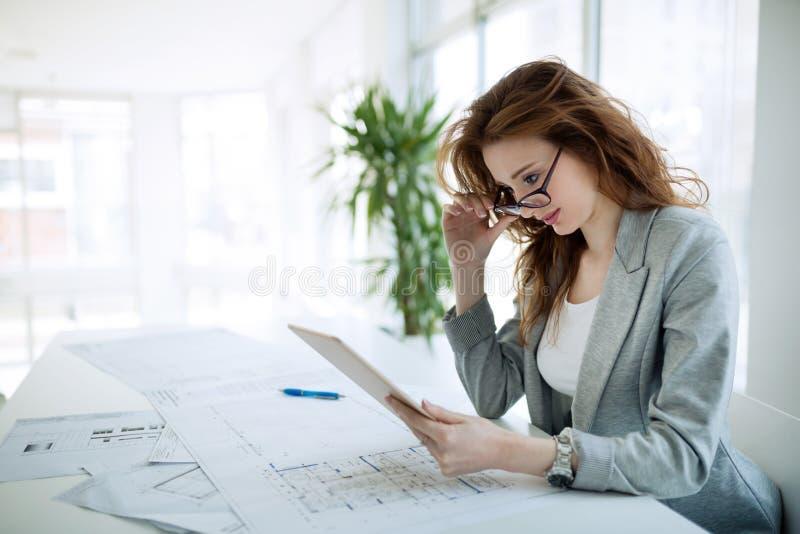 Schöner weiblicher Architekt, der im Büro arbeitet lizenzfreie stockbilder