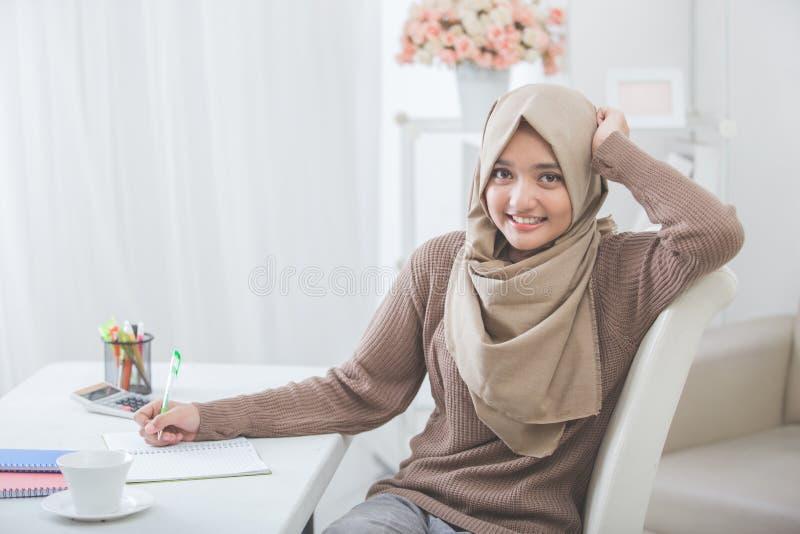 Schöner weiblicher asiatischer Student mit dem hijab, das Hausarbeit tut stockbilder