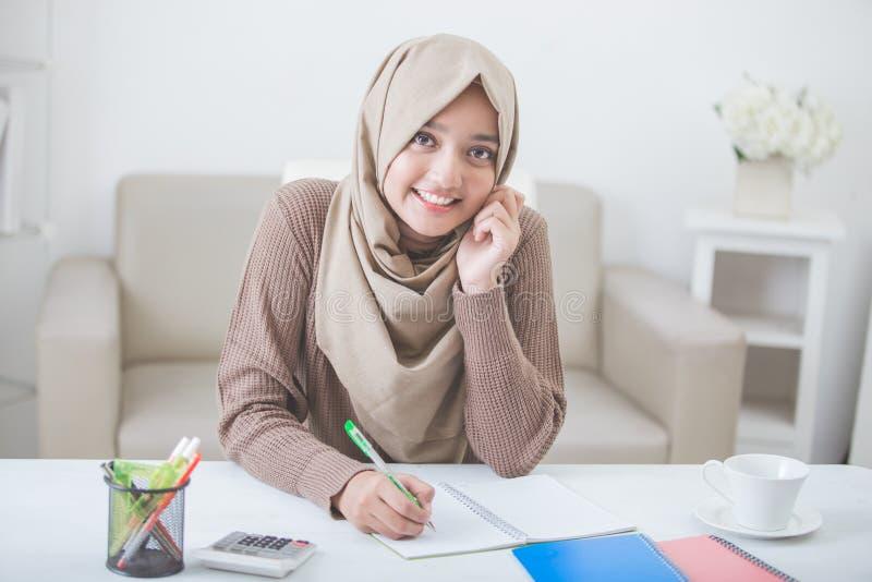 Schöner weiblicher asiatischer Student mit dem hijab, das Hausarbeit tut lizenzfreie stockbilder