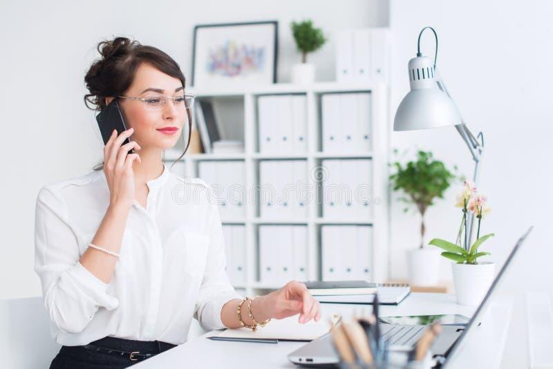 Schöner weiblicher Assistent, der unter Verwendung des Mobiltelefons nennt Junger Büroangestellter, der am Handy hat Geschäft spr stockfoto