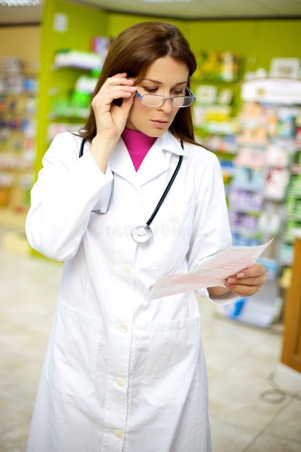 Schöner weiblicher Doktor, der in der Apotheke arbeitet stockbilder