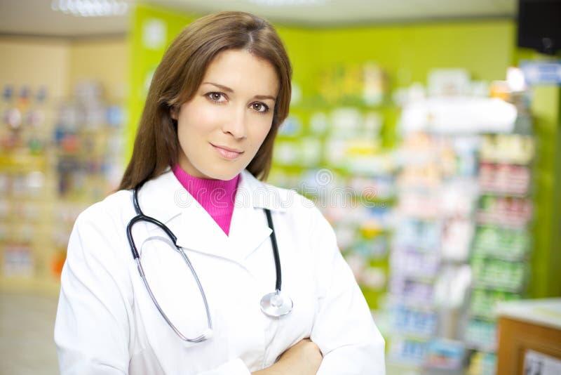 Schöner weiblicher Doktor, der in der Apotheke lächelt lizenzfreies stockbild