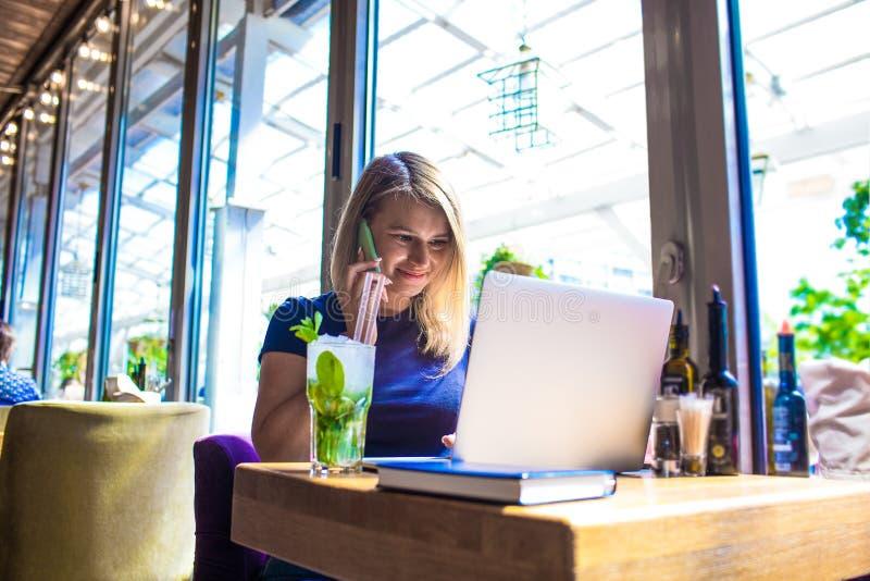 Schöner weiblicher erfahrener Werbetexter, der Mobiltelefon und netbook verwendet stockfotografie