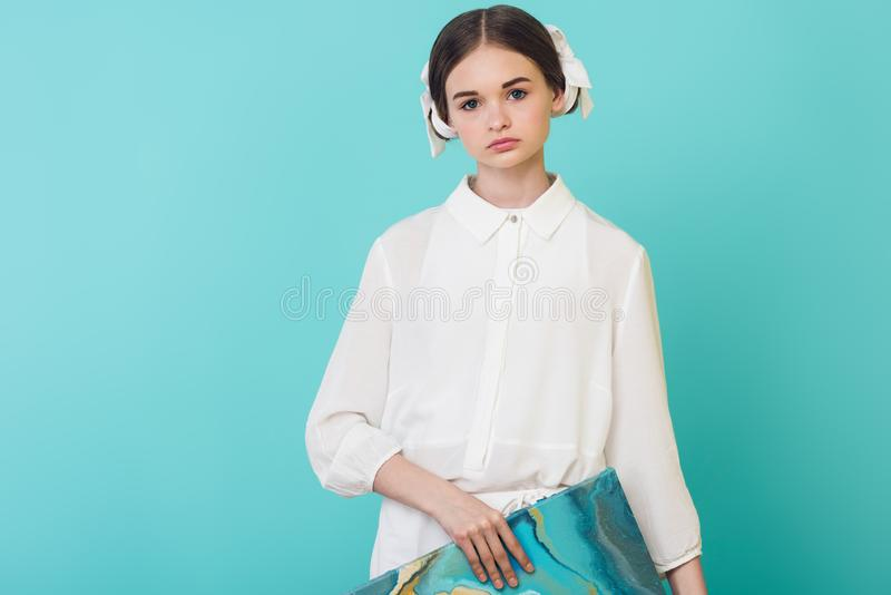 schöner weiblicher Jugendlicher in der weißen Ausstattung, die Ölgemälde hält stockfoto