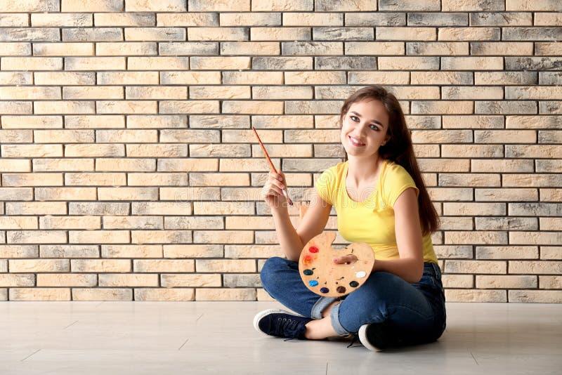 Schöner weiblicher Künstler, der auf Boden gegen Backsteinmauer sitzt lizenzfreie stockfotos