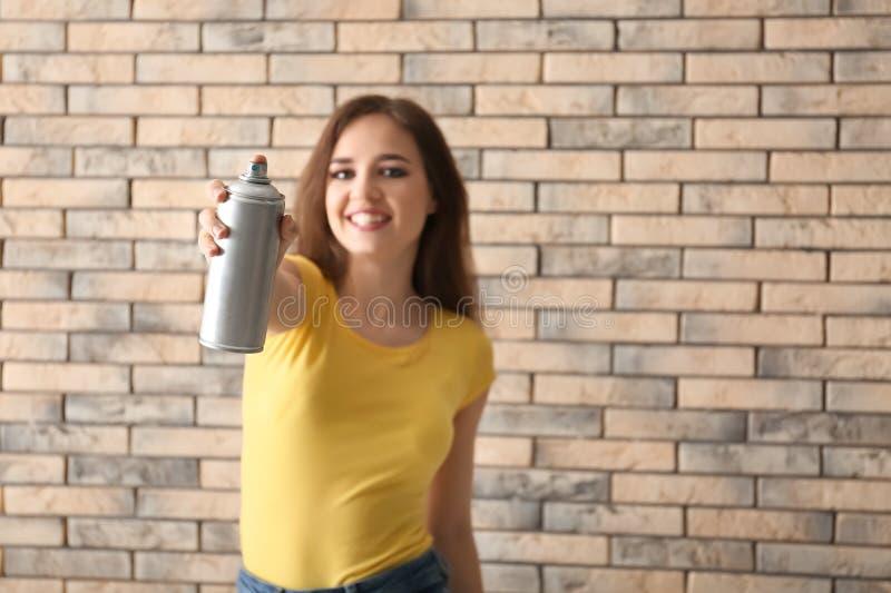 Schöner weiblicher Künstler mit Sprühfarbe gegen Backsteinmauer lizenzfreies stockfoto
