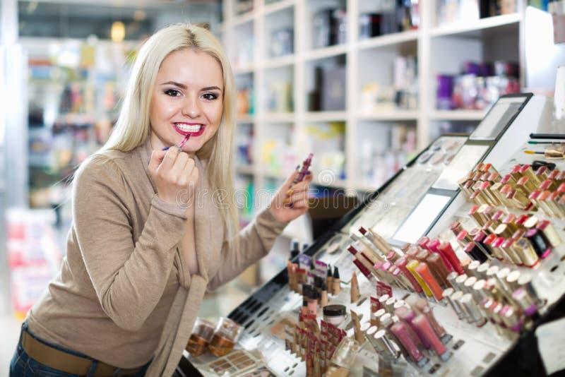 Schöner weiblicher Kunde, der roten Lippenstift im Make-upabschnitt kauft stockbilder