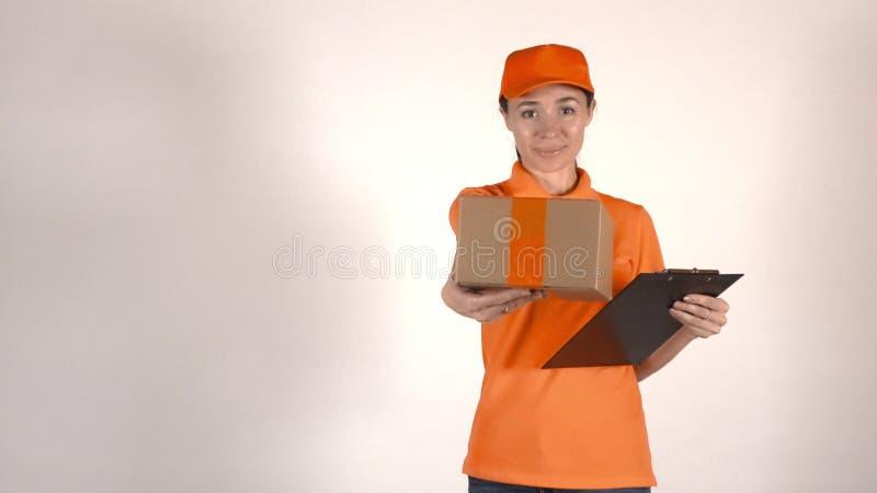 Schöner weiblicher Kurier in der orange Uniform, die ein Paket liefert Hellgraues backround, lizenzfreie stockbilder
