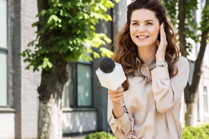 schöner weiblicher Nachrichtenreporter, der Interview nimmt lizenzfreies stockfoto