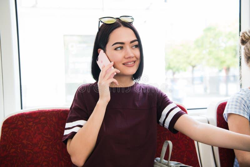 Schöner weiblicher Pendler, der am Handy beim Nehmen des Busses zur Arbeit spricht stockfoto