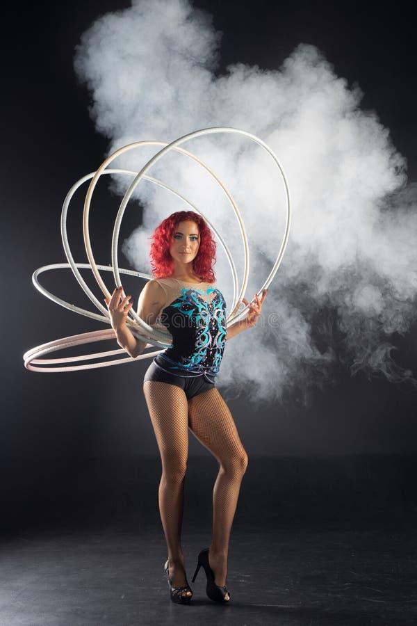 Schöner weiblicher roter Haarzirkuskünstler, der Bänder hält stockfotos