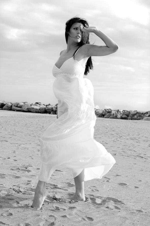 Schöner weiblicher Tänzer, der auf dem Strand mit weißes Kleiderschwarzweiss-Porträt aufwirft lizenzfreies stockfoto