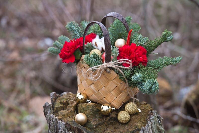 Schöner Winterblumenstrauß der Fichte, der Äpfel, der Gartennelken und der Baumwolle stockfoto