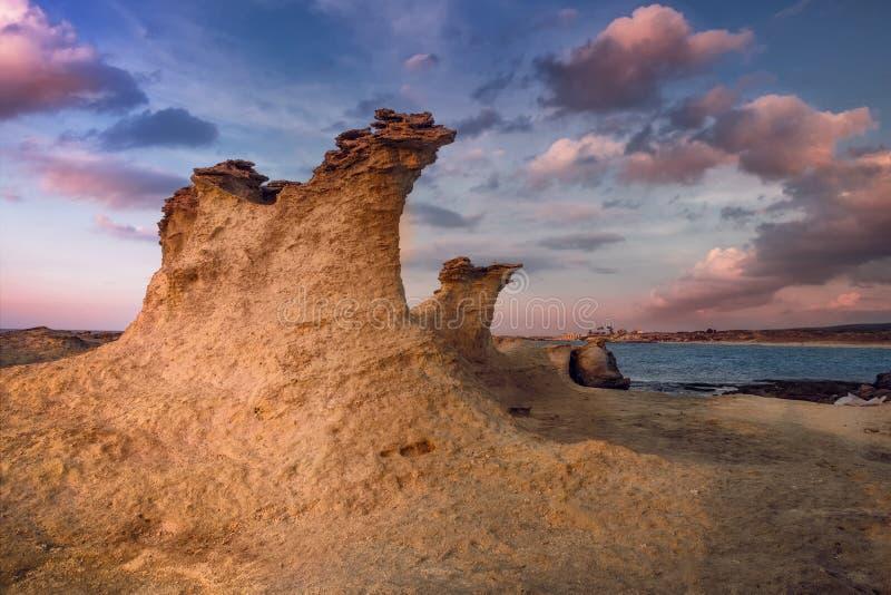Schöner Zypern-Sonnenuntergang auf der leeren felsigen Küste der Wüste mit merkwürdigen fiqures am Halk-Strand lizenzfreie stockfotos