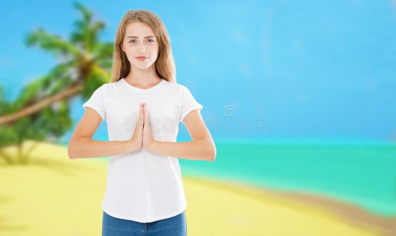 Schönes übendes Yoga der jungen Frau im Strand, der namaste mudra tropisch und gemacht worden sein würden lizenzfreies stockfoto