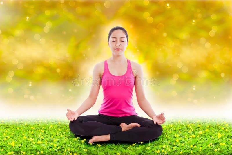 Schönes übendes Yoga der jungen Frau, sitzend in einem Lotos positi stockfoto
