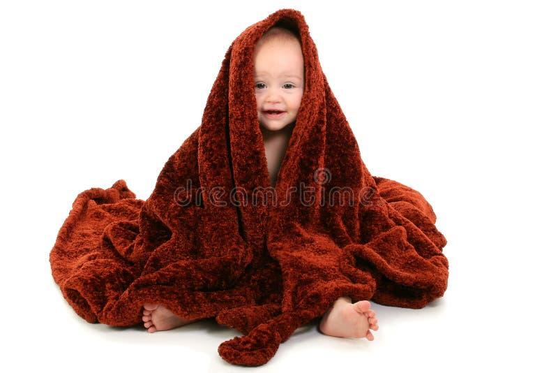 Schönes 10 Monats-altes Schätzchen eingewickelt in der Brown-flockigen Decke lizenzfreie stockfotografie
